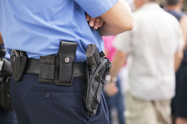 Midsection of police officer with handgun and handcuffs
