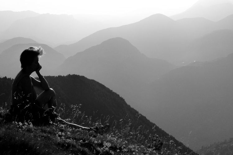 Silhouette of woman sitting on rock against mountains