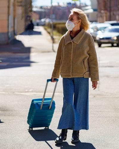 Senior 60s woman with blue suitcase traveling alone during coronavirus epidemic
