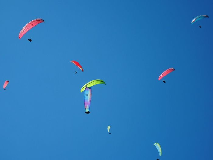Low Angle View Of Parachutes Flying Against Clear Blue Sky