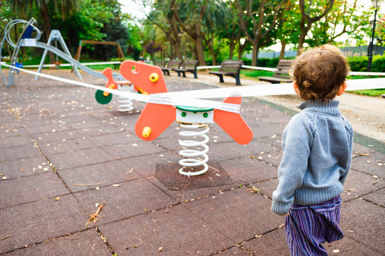 Rear view of boy playing on footpath at park