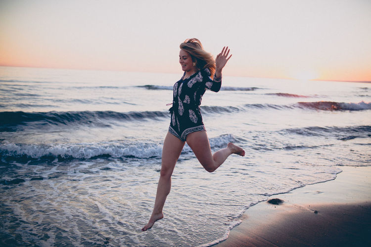 Beach Beautiful Woman Beauty In Nature Front View Full Length Happiness Horizon Over Water Jumping Leisure Activity Lifestyles Motion Nature One Person Outdoors Real People Sand Sea Sky Smiling Sunset Vacations Water Wave Young Adult Young Women