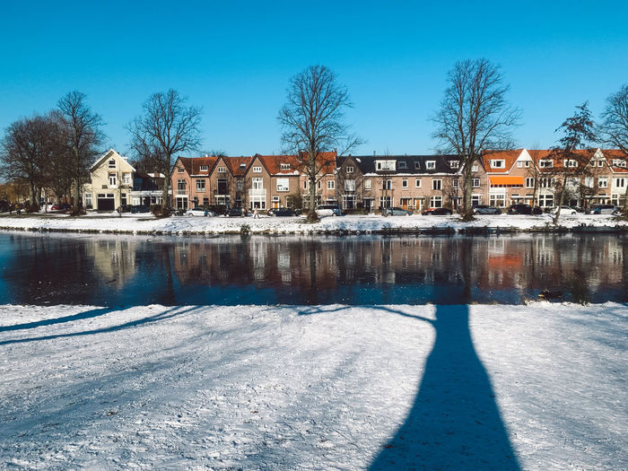 Buildings by frozen lake against sky during winter