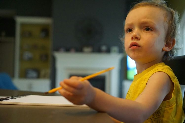 Boy Holding Pencil While Sitting On Table At Home