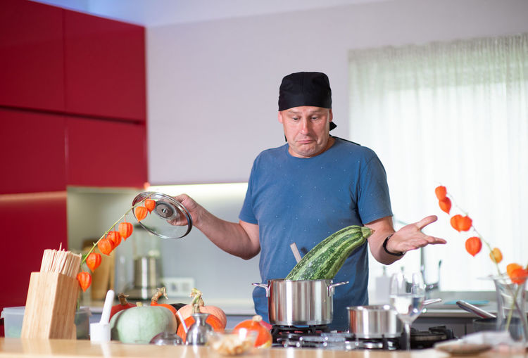 Man looking at vegetable in container on stove