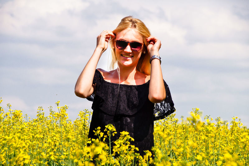 Portrait Of Smiling Young Woman Wearing Sunglasses On Oilseed Rape Field