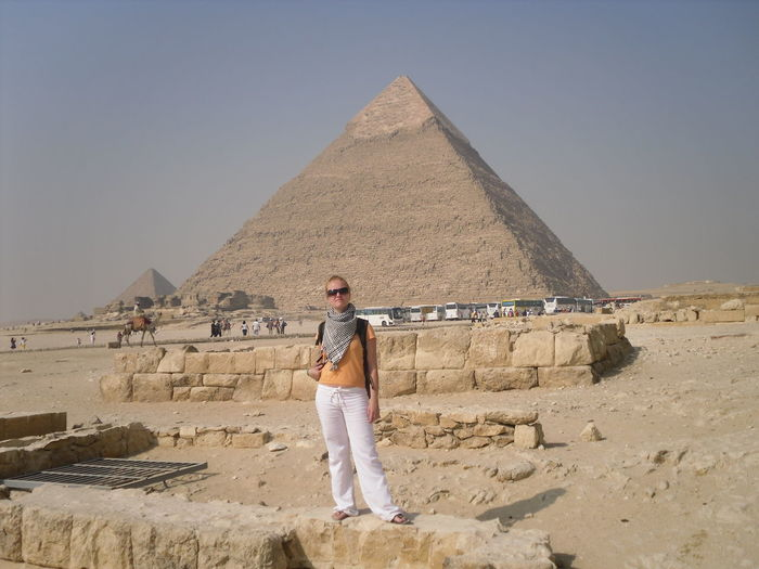 Young woman standing by giza pyramids against clear sky