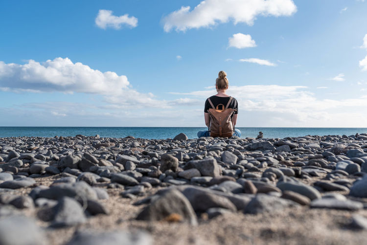 Rear view of backpack woman sitting on beach against sky