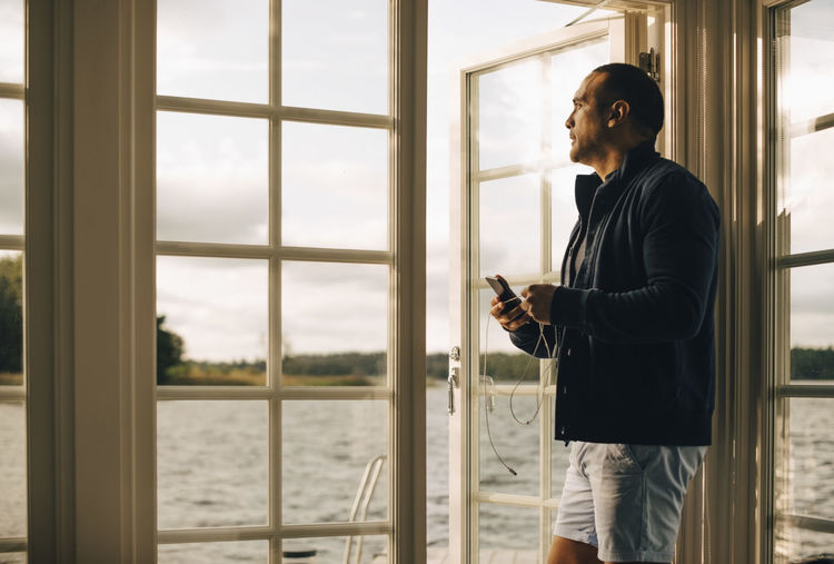 Man looking at camera while standing on window