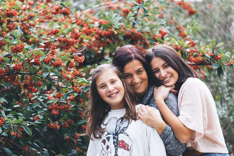 Bonding Casual Clothing Childhood Daughter Day Family Flower Girls Happiness Leisure Activity Lifestyles Looking At Camera Love Mother Nature Outdoors Plant Portrait Real People Smiling Standing Togetherness Women Young Women