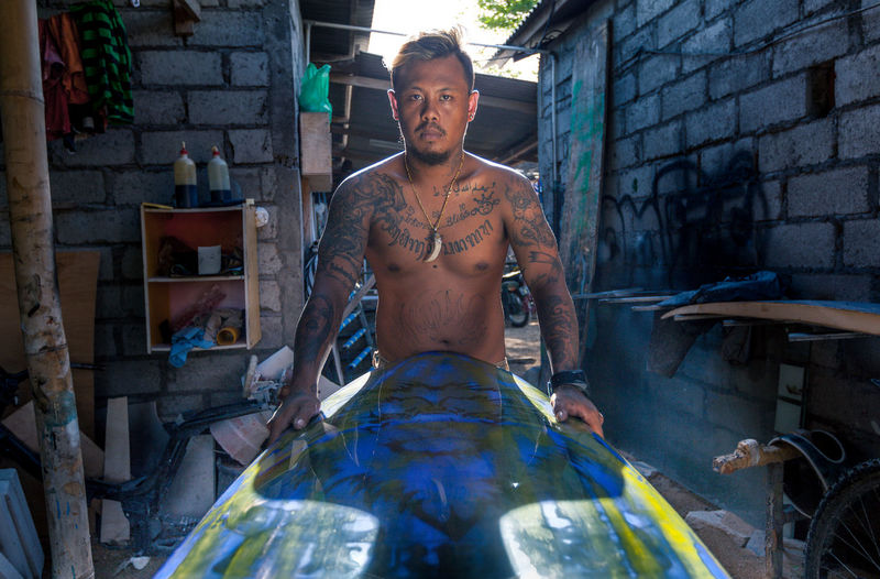 Portrait Of Serious Tattooed Man Holding Surfboard