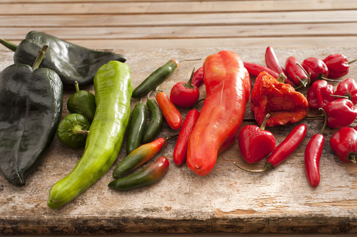 Large selection of fresh chili peppers of different varieties and colors displayed on a wooden kitchen counter, used as a pungent spice in cooking Abundance Assortment Capsicum Cayenne Chili  Chili Pepper Chilling Cooking Different Displayed Flavoring Fresh Green Hot Ingredient Jalapeno Peppers Pungent Red Red Seasoning Spice