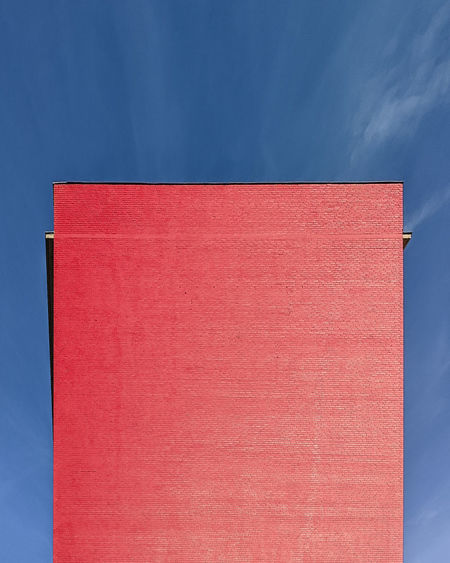 Low angle view of red wall against blue sky