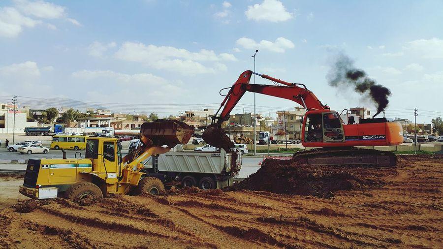 Bulldozer loading dump truck at construction site