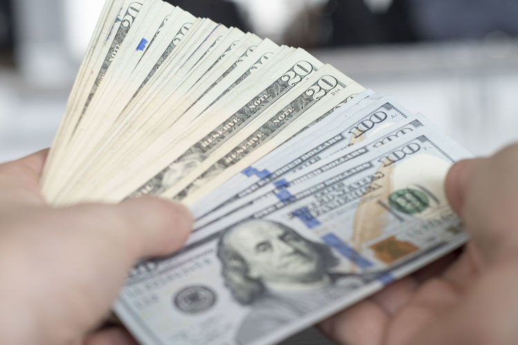 Cropped image of hand holding us paper currency