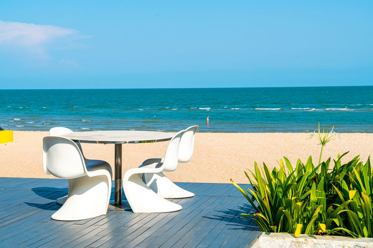 Chairs and table on beach against blue sky