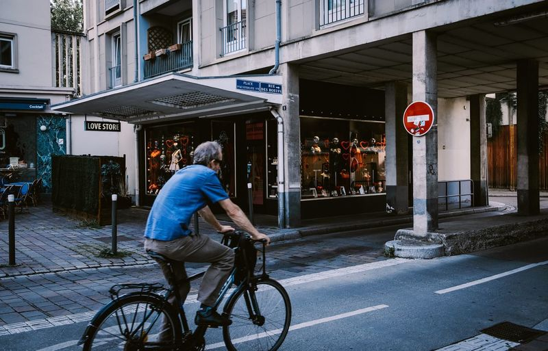 Tour de France ... Urban Perspectives Street Photography The Devil's In The Detail Architecture Bicycle Building Exterior Built Structure Transportation City Real People One Person Street Men Text Communication Sign Lifestyles Riding Land Vehicle Mode Of Transportation Road Ride The Street Photographer - 2019 EyeEm Awards