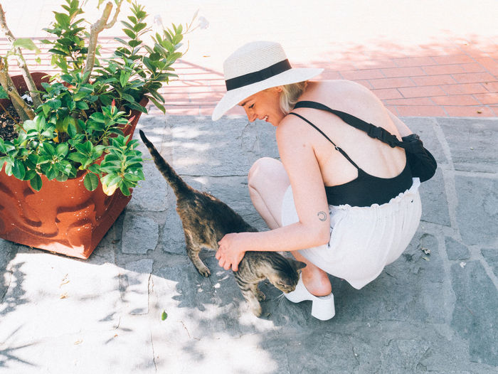 Side view of woman sitting on potted plant