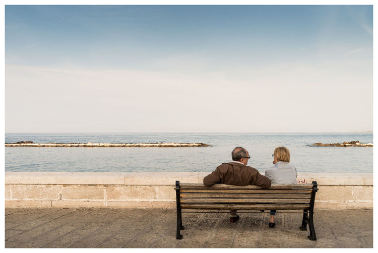 Rear View Of Senior Couple Sitting On Bench At Promenade Against Clear Sky
