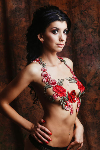 Portrait of shirtless young woman with floral decoration standing against wall