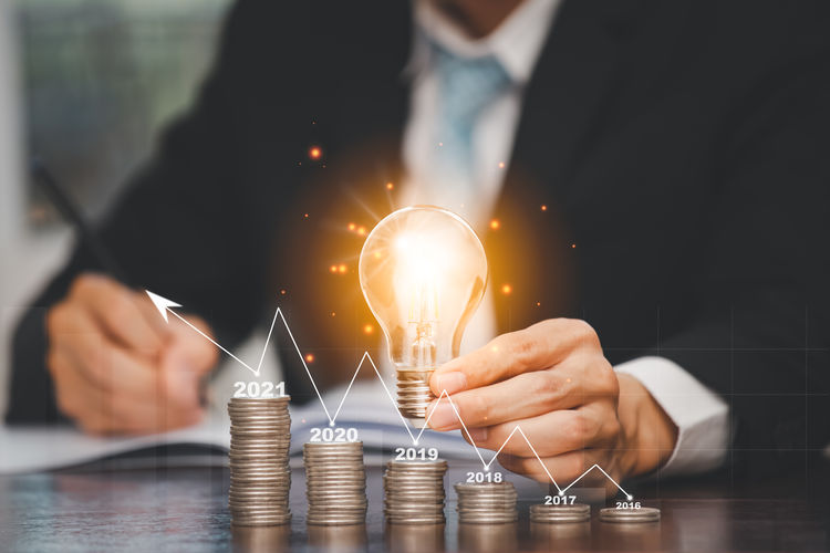 Cropped image of man holding light bulb on table
