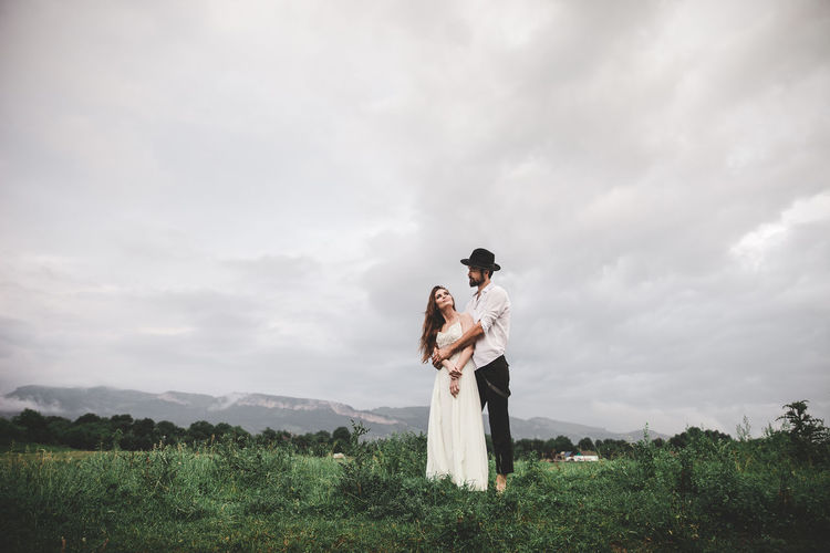 Beautiful young couple in love walking in nature. He hugs her from behind. They are happy. She is dressed in a white wedding dress, and the groom wears a black hat and is dressed in a shirt and pants with suspenders. He has a beard on his face. Photo of two attractive people. The grass grows in the meadow. Above the head is the sky with clouds. Full length photo. Couple Family Fashion Freedom Happiness Happy Happy People Lifestyle Love Nature Peole And Places Relationship Wedding Couple - Relationship Couple In Love Happy Time Leasure Activity Lifestyles Peolpe Together Together Forever Togetherness Two People Wedding Day Wedding Dress