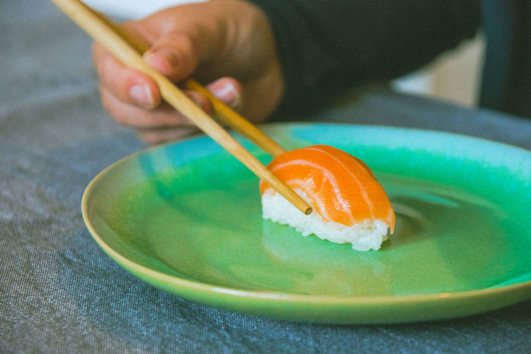 Eating salmon sushi Asian Food Chopsticks Close-up Finger Food Food And Drink Freshness Hand Healthy Eating Holding Human Body Part Human Hand Indoors  Japanese Food One Person Ready-to-eat Real People Rice Selective Focus Unrecognizable Person Wellbeing
