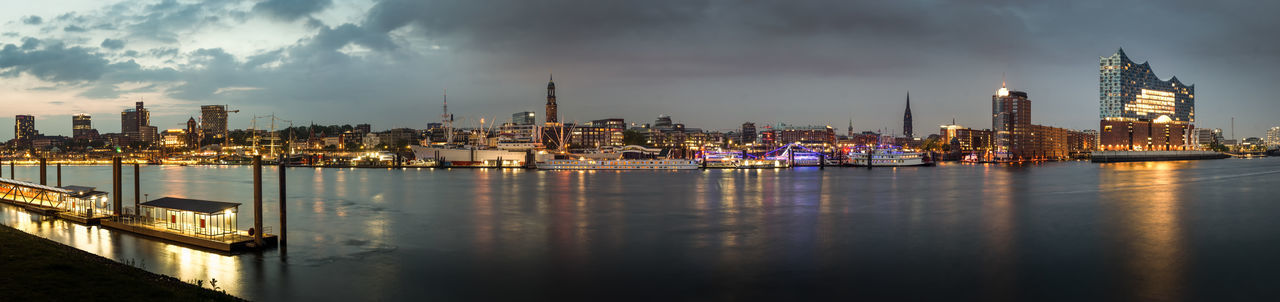 Panoramic view of illuminated buildings by river against sky