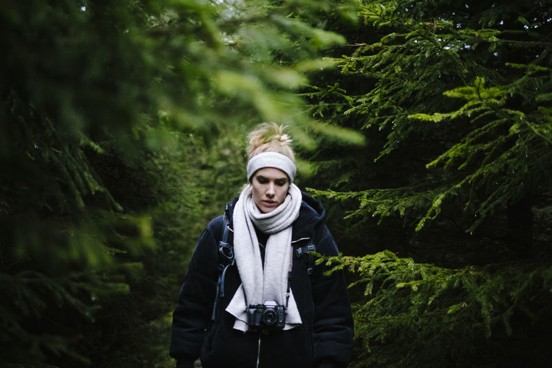 Full length of young woman standing by tree in forest