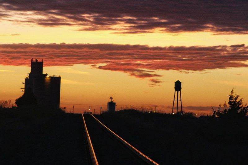 Sunset Kansas Does It Best No Place Like Home My Hometown Rural America Small Town Living Train Tracks Water Tower Grain Elevator Sky No People Built Structure Cloud - Sky Silhouette Architecture City Nature Outdoors Building Exterior Beauty In Nature Day Transportation