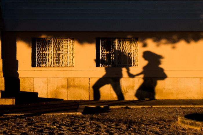 SHADOW OF MAN WALKING ON STREET AT SUNSET