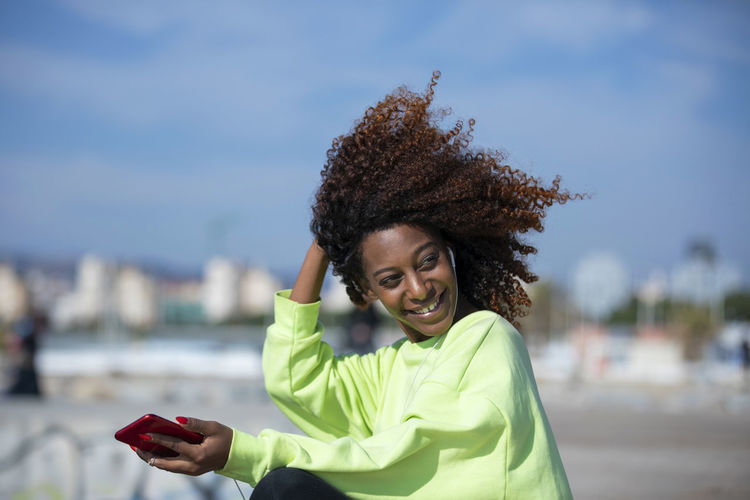 Side view of a young curly afro woman sitting on breakwater rocks enjoying and smiling while using a mobile phone to listen music in a sunny day One Person Smiling Happiness Portrait Curly Hair Young Adult Looking At Camera Women Real People Smart Phone Focus On Foreground Technology Adult Wireless Technology Lifestyles Day Portable Information Device Standing Mobile Phone Hairstyle Hair Human Arm Beautiful Woman Outdoors Woman African American Afro Denim Happiness Happy Fun Daylight Sunlight