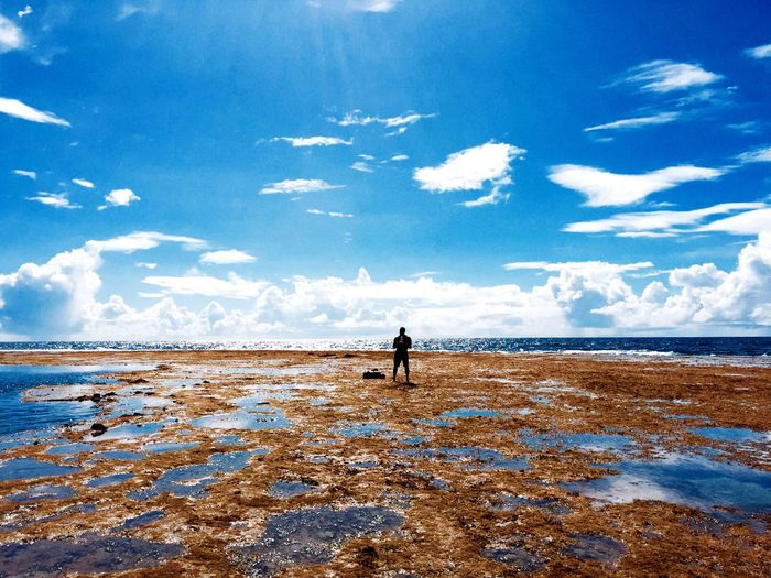 Man At Beach Against Cloudy Sky During Sunny Day