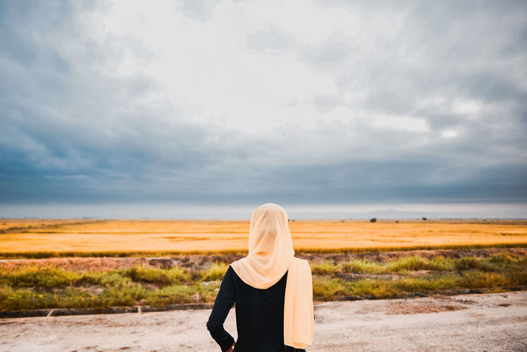 Rear View Of Teenage Girl Looking At Landscape Against Cloudy Sky