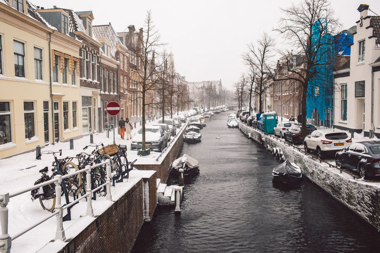 Canal amidst buildings in city during winter