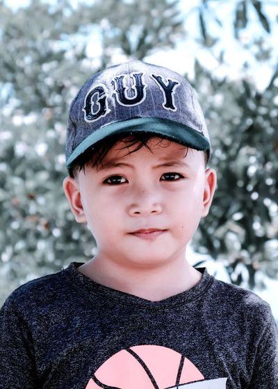 Close-up portrait of boy wearing cap against tree