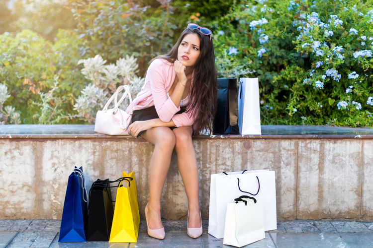Exhausted, pretty woman takes a break after shopping in the city Shopping Stress Bag Bags Beautiful Woman Casual Clothing Clothing Concept Consumerism Exhausted Fashion Front View Hair Leisure Activity Lifestyles Long Hair Maniac Model One Person Resting Shopping Shopping Bag Sitting Tired Young Adult