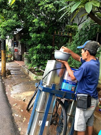 Sidewalk Outdoors Outdoor Photography Men Mature Adult At Work Retail  Capture The Moment Jakarta Indonesia Hands At Work Person Holding Full Frame Cans Transportation Land Vehicle Mode Of Transport Bicycle Green Color Under The Trees After The Rain Casual Clothing Natural Streetphotography Street Photography