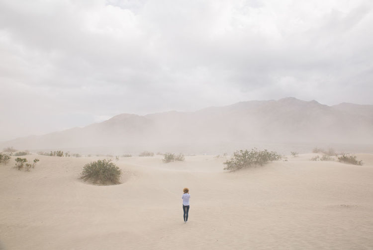 Rear view of woman standing at death valley against sky during sandstorm