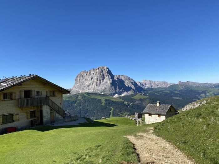 Scenic view of houses and mountains against clear blue sky