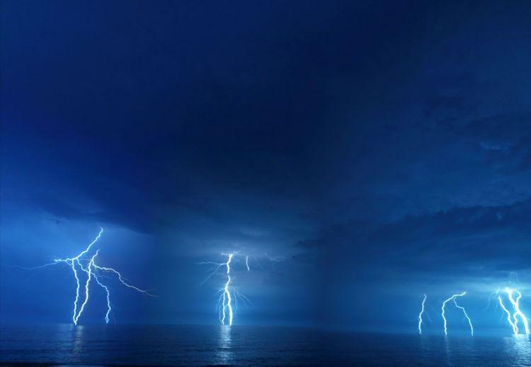 Lightning over sea against blue sky at night