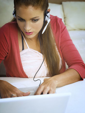 caucasian woman using laptop At Home Online Gaming Blond Hair Casual Clothing Caucasian Charting Communication Connection Ear Phone Headphones Indoors  Laptop Leisure Activity Microphone Occupation One Person Onlline Real People Sitting Technology Telecommunications Equipment Using Laptop Wireless Technology Young Adult Young Women
