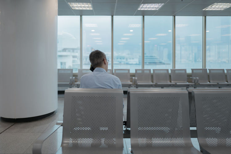 Rear View One Person Men Sitting Office Window Seat Business Indoors  Real People Business Person Chair Adult Corporate Business Businessman Males  Headshot Table Day
