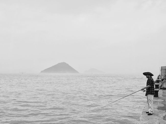 Sea Water Scenics One Person Tranquility Beauty In Nature Real People Outdoors Day Horizon Over Water Waterfront People And Places Foggy Day Capturing The Moment Olympus OM-D EM-1 Light And Shadow Leisure Activity Victoria Harbour Island Man Fishing Black And White Black & White