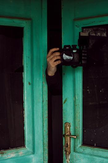 Man holding closed door of building