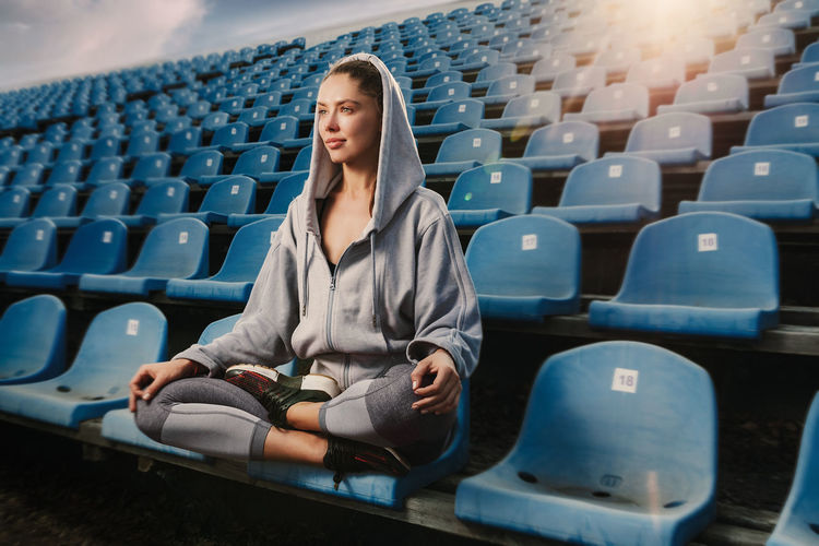 A beautiful sports girl after a hard workout took a break. Meditates in the lotus position Meditation Tranquility Yoga Yoga Pose Casual Clothing Chair Day Front View Indoors  Leisure Activity Lifestyles Looking Lotus Position One Person Real People Seat Sitting Sport Stadium Successful Women Yoga Lotus Young Adult Young Women Zen