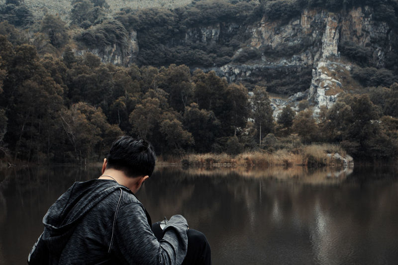 man sitting by lake against trees