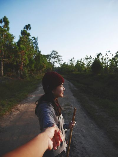 Cropped Image Of Man Holding Hands With Girlfriend On Road Against Clear Sky