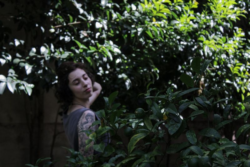 Side view of young woman standing by plants