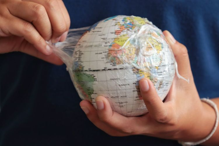 Midsection of man holding globe in plastic bag